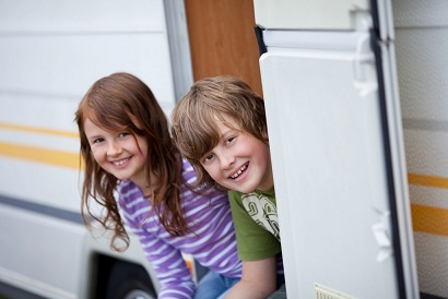 zwei kinder sitzen am wohnwagen