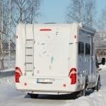 Wohnmobil auf einer verschneiten Landstraße