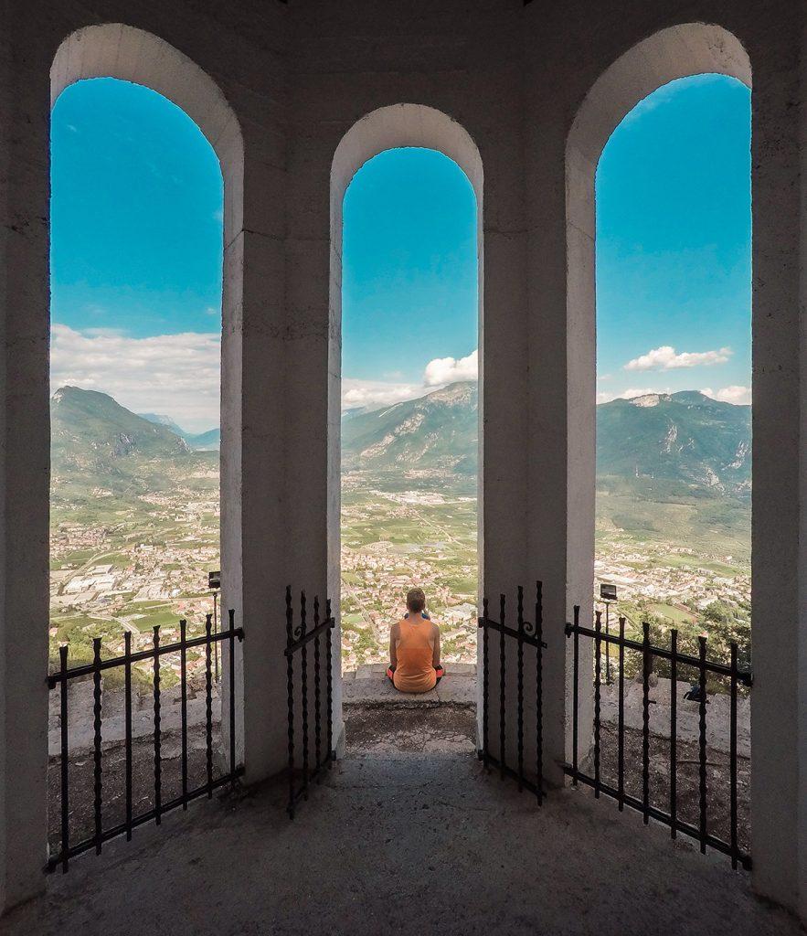 Eine Person sitzt auf einer Aussichtsplattform mit Blick auf Riva del Garda am Gardasee.