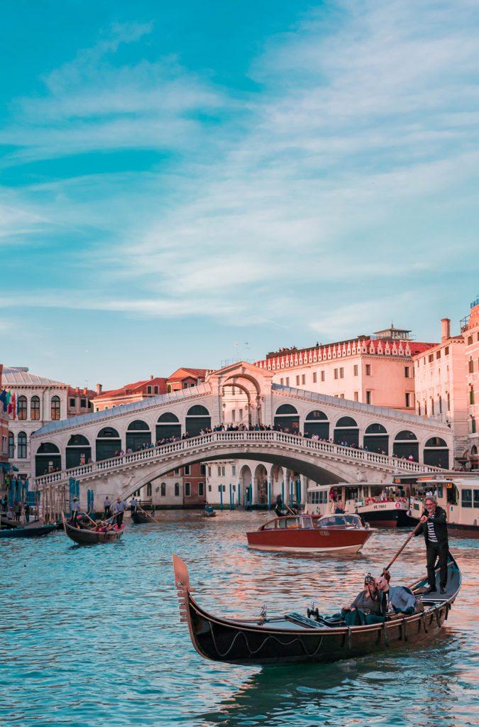Eine Gondola mit einem Gondoliere und einem Paar vor einer Brück in Venedig.