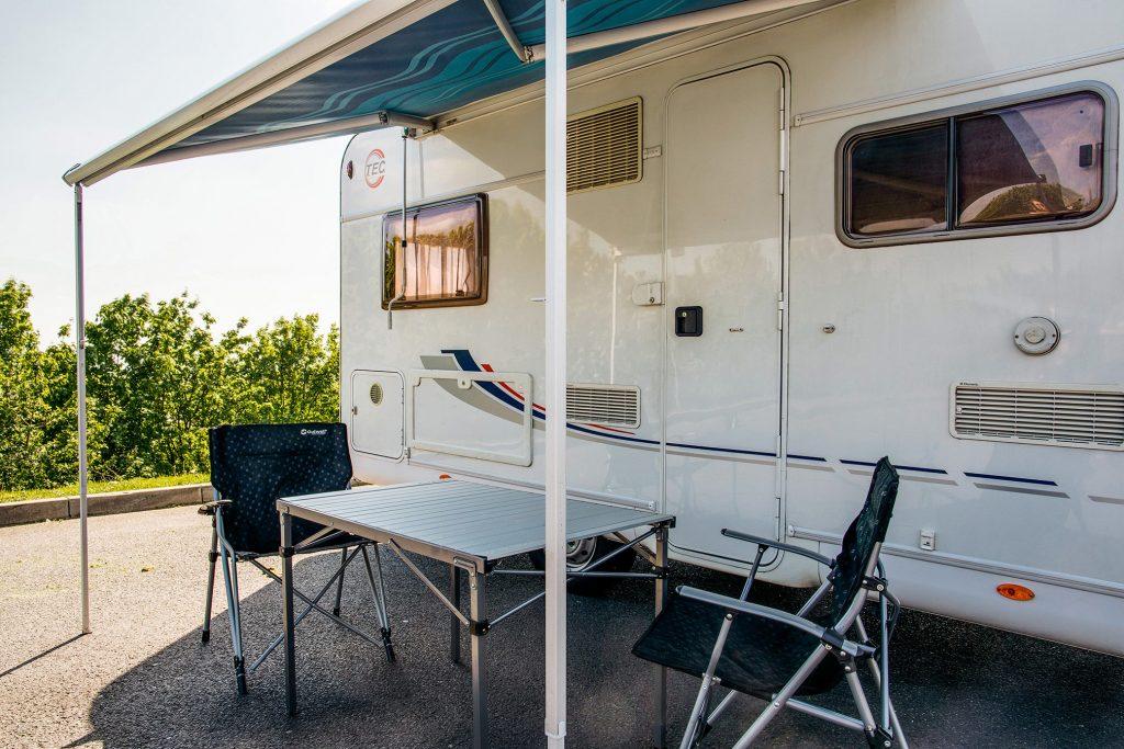 Wohnmobil mit Markise und Campingmoebeln