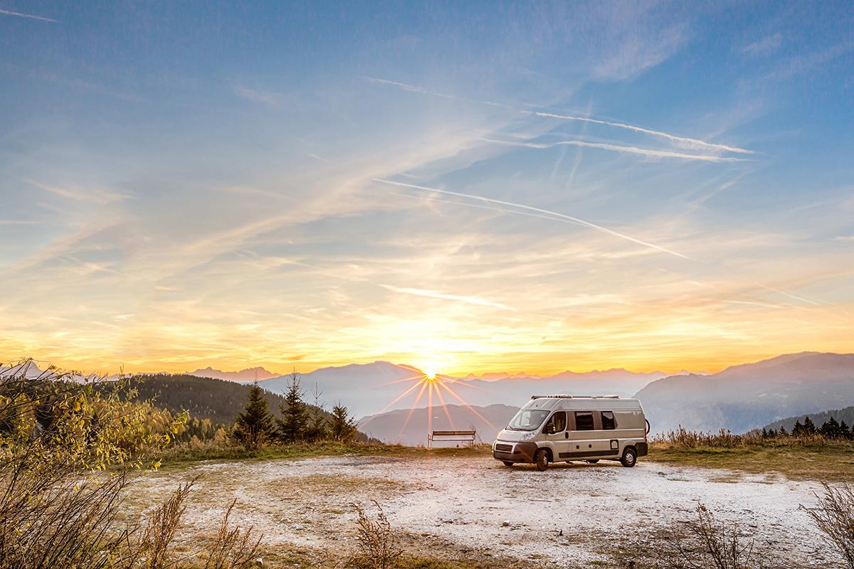 Wohnmobil vor Berglandschaft bei Sonnenuntergang