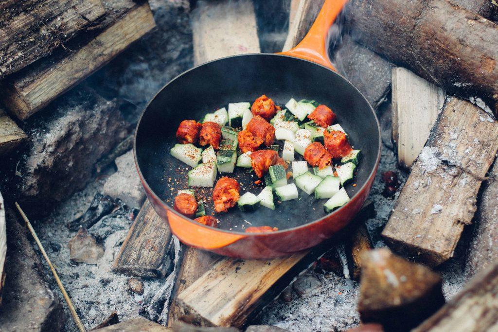 Pfanne, die mit verschiedenem Gemüse gefüllt auf einem Lagerfeuer steht.