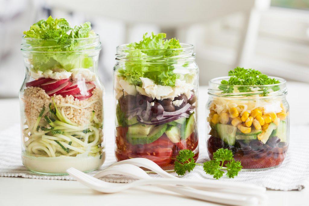 Schraubgläser, die mit verschiedenen Salaten gefüllt sind.