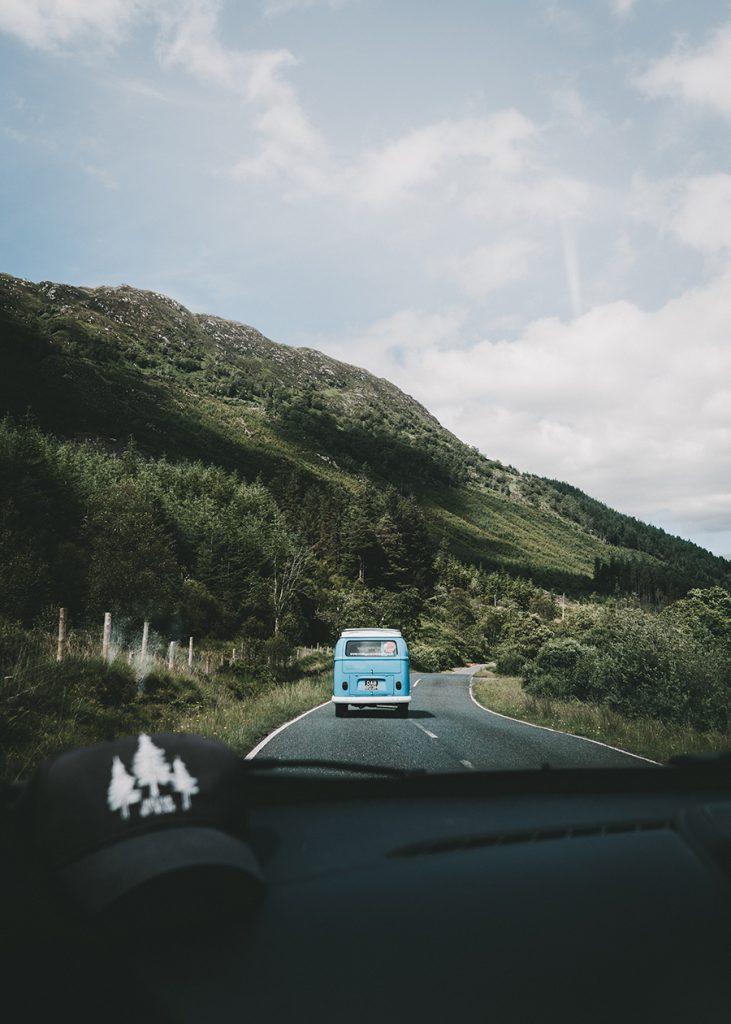 Ein blauer Camper fährt auf einer Straße, die durch bergige Landschaft fährt.
