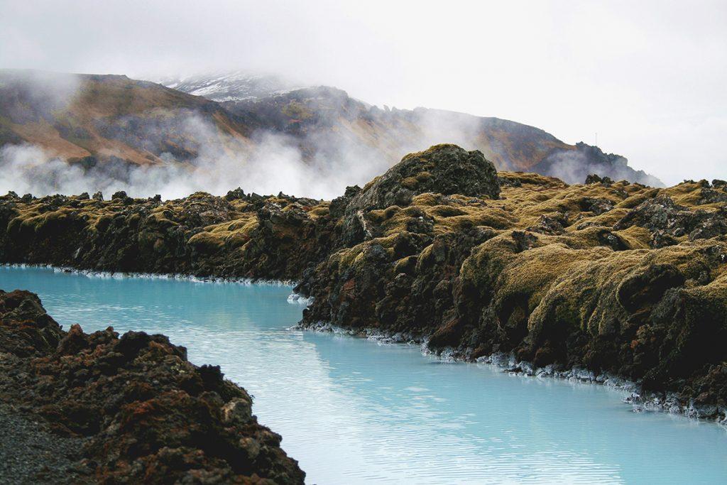 Karge, bemooste Landschaft mit heißen Quellen und hellblauem Wasser in Island.