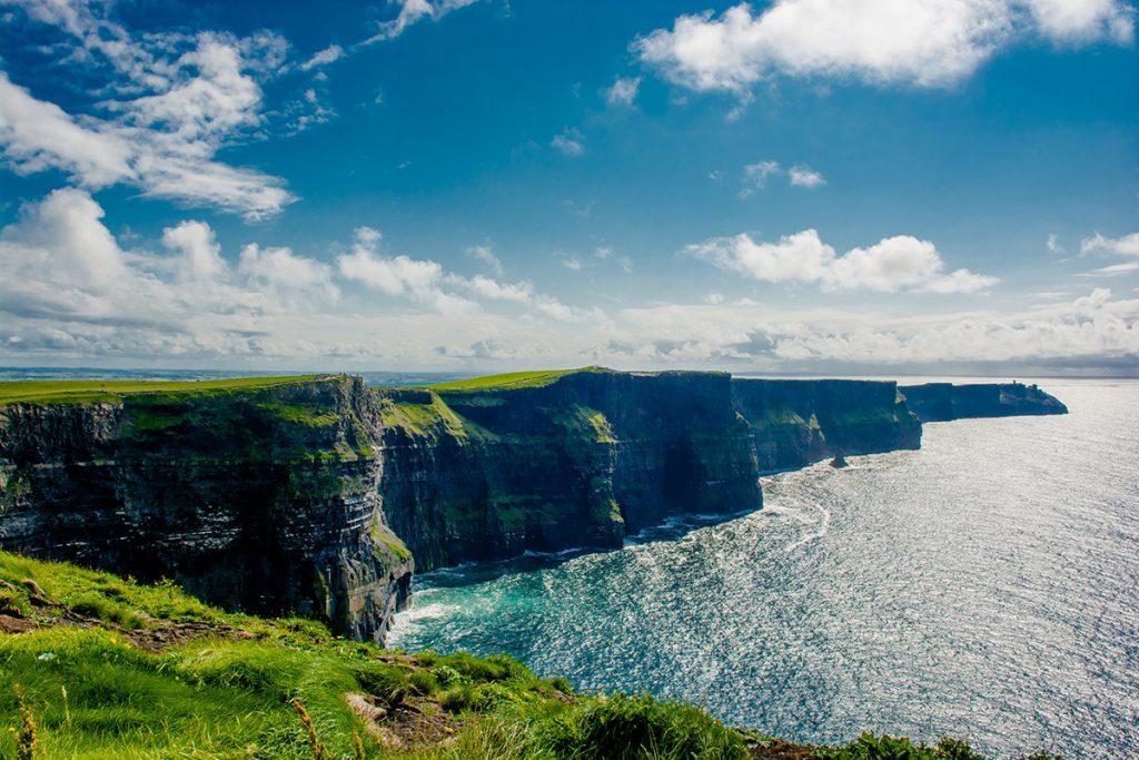 Grüne Fläche, Steilklippen und der Ozean in Irland.