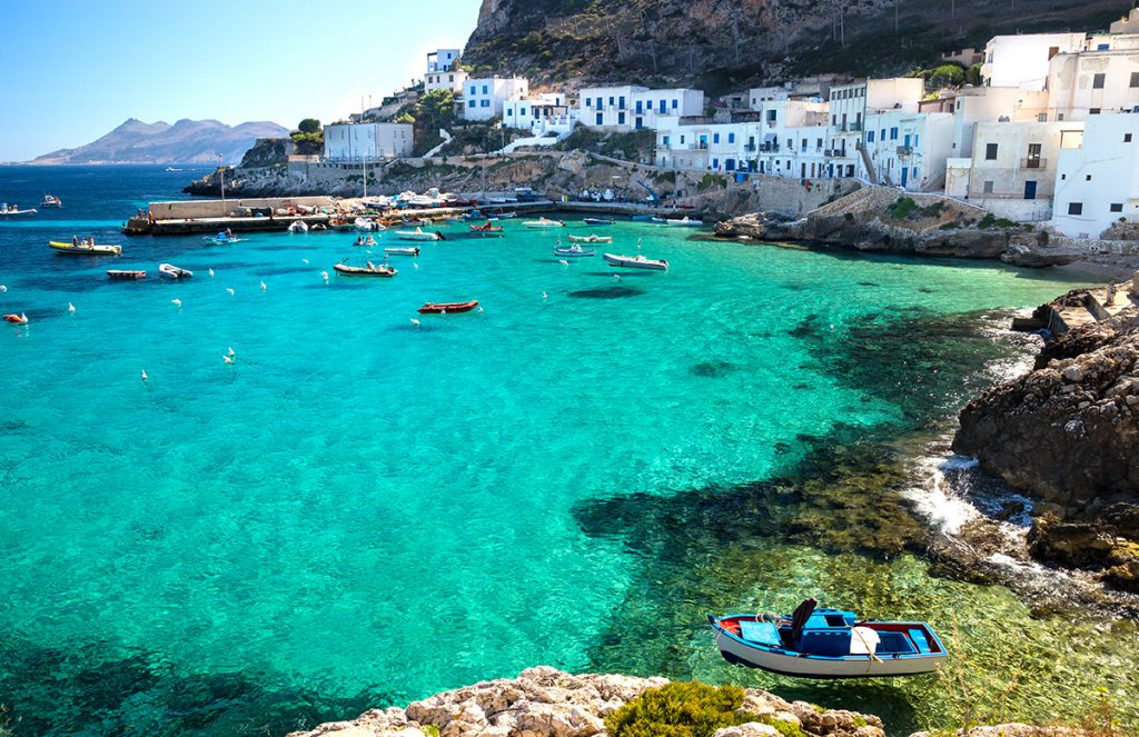Bucht mit klarem, blauen Wasser und weißen Häusern auf Sizilien.
