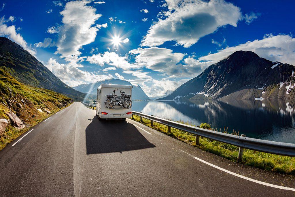 Ein Wohnmobil fährt entlang eines Fjordes in Norwegen.