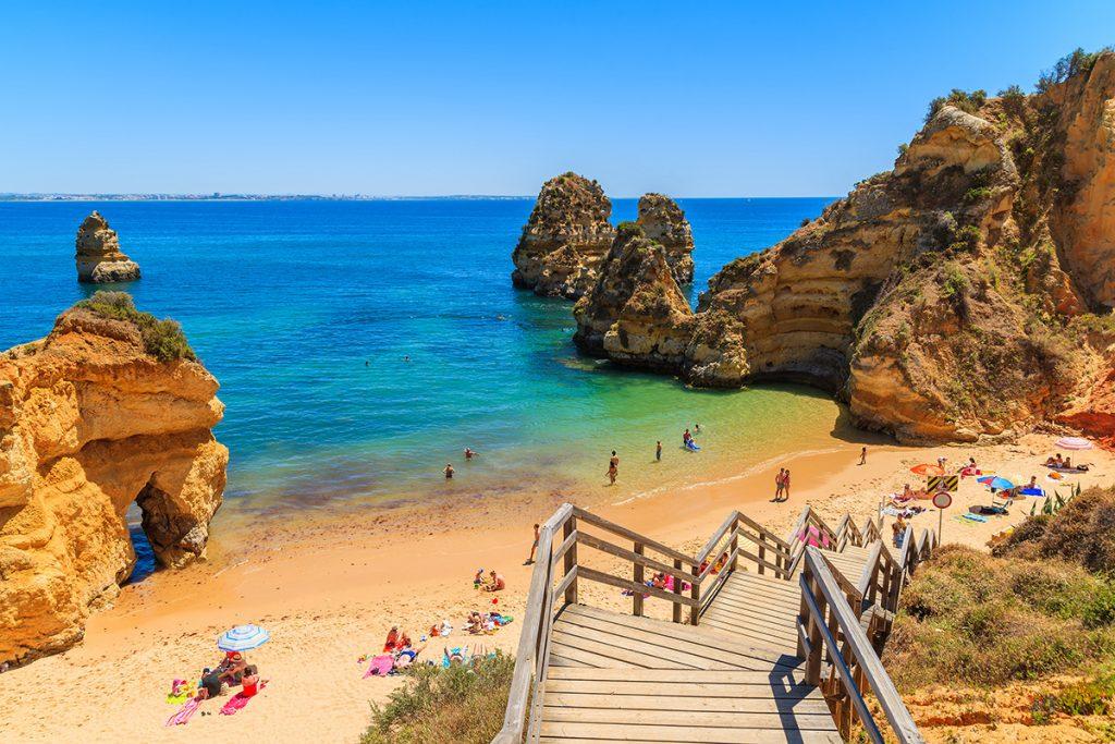Ein Strand an blauem Wasser und großen Felsen in der Algarve.