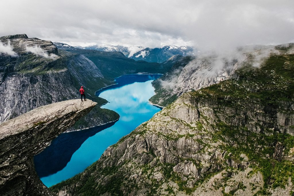 Eine Person steht am Rand einer Klippe über einem Fjord.