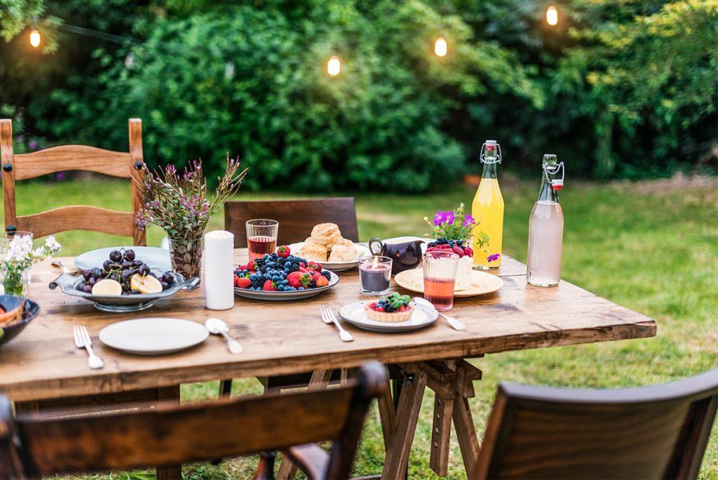 Ein mit Obst und Gebäck gedeckter Holztisch und Stühle in einem Garten.