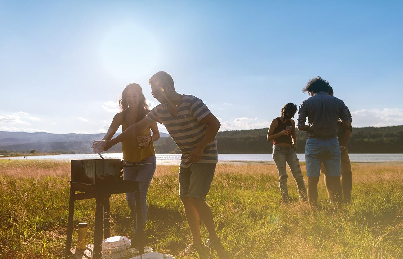 Freunde grillen bei Sonnenuntergang am See