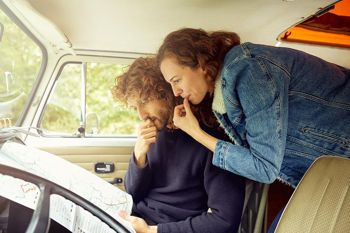 Pärchen mit Landschaftskarte in der Fahrerkabine eines Campers.