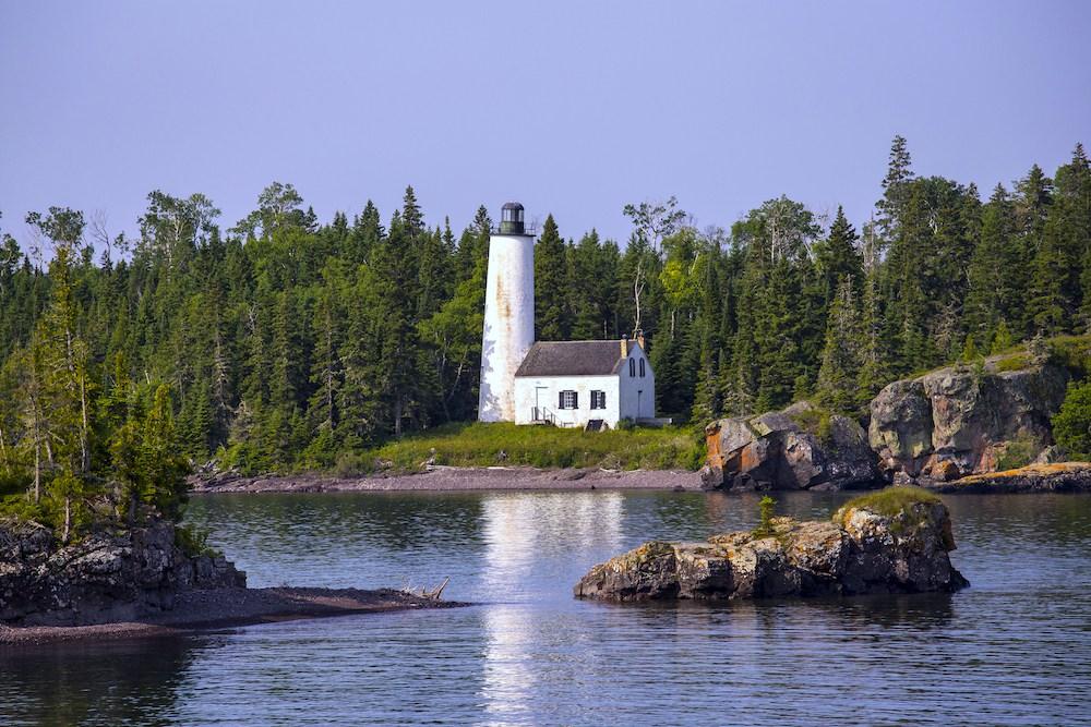 Ein Leuchtturm. Im Vordergrund sind kleine Felsinseln im Wasser zu sehen.