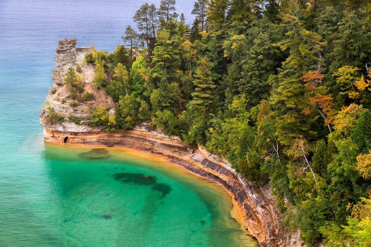 Blick von oben auf Miner's Caste, eine Felsformation, die in das türkise Wasser des Lake Superior hervorsticht.
