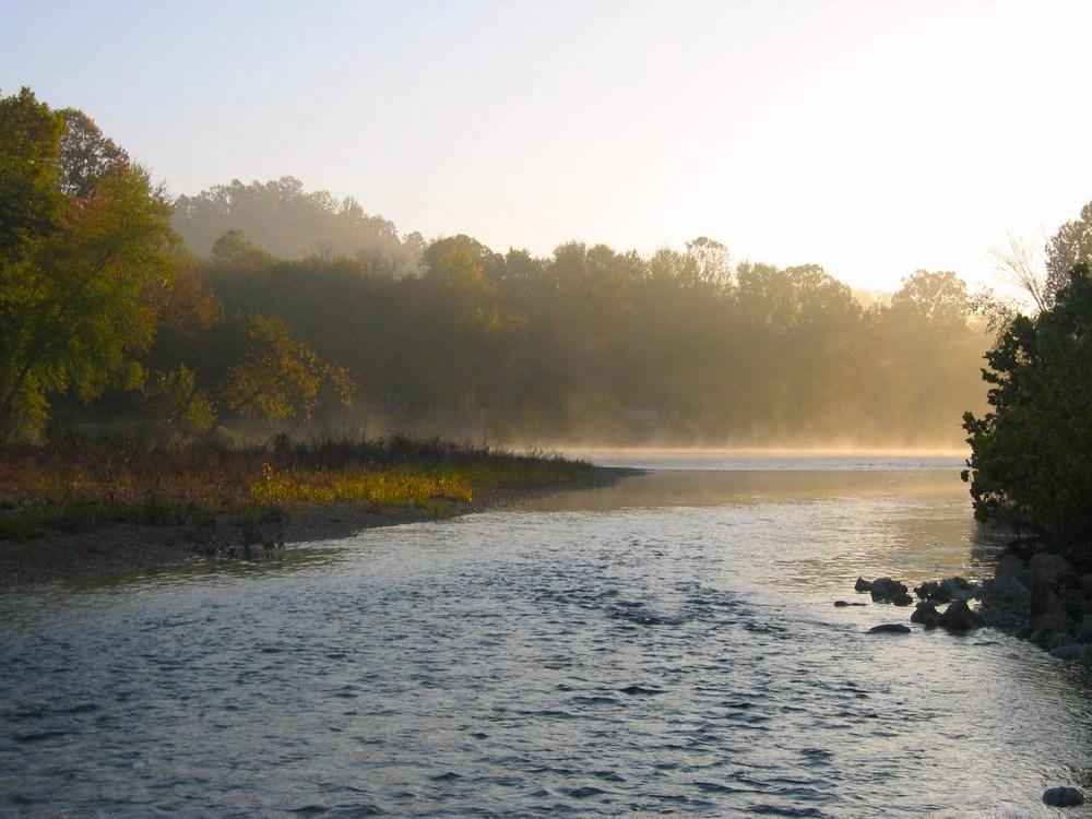 Ein von Bäumen gesäumter Fluss bei Sonnenaufgang im Ozark National Scenic Riverways.