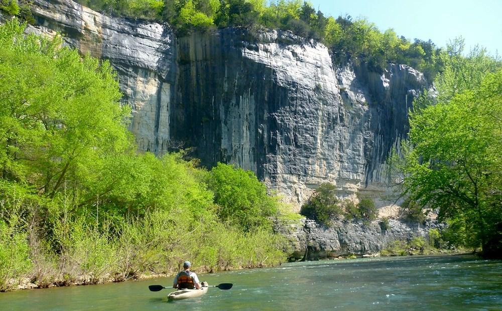 Ein Mann im Kajak auf dem Buffalo River, vor einem felsigen Steilufer.