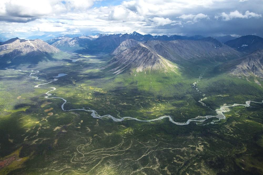 Blick aus der Vogelperspektive auf den Wrangell-St Elias Nationalpark: Es sind Bergketten,ein Tal und Flüsse zu sehen.