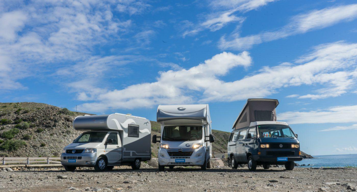 Zwei Alkoven Wohnmobile stehen neben einem VW-Campervan.