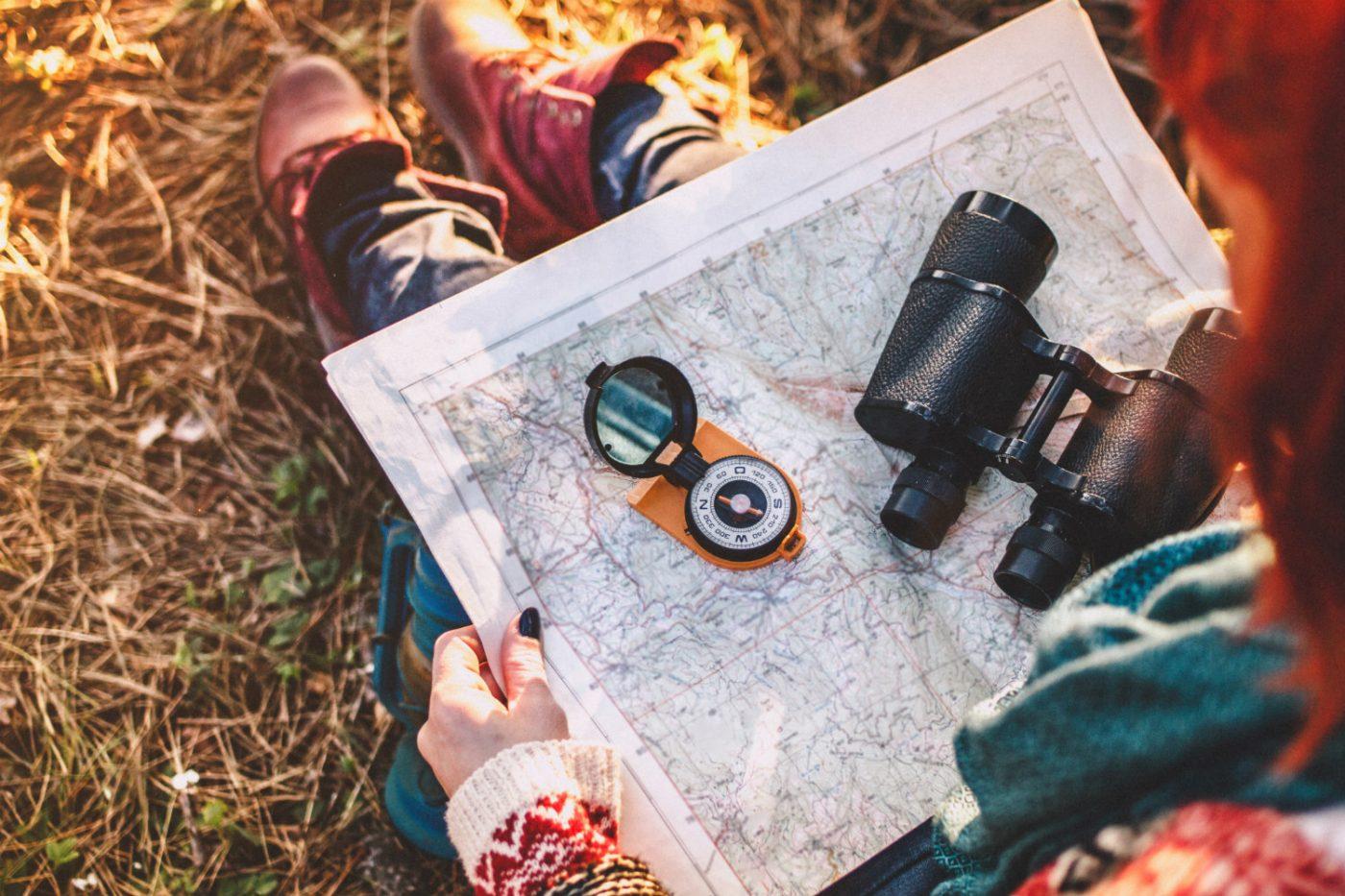 Eine Straßenkarte, auf der ein Kompass und ein Fernglas liegen.