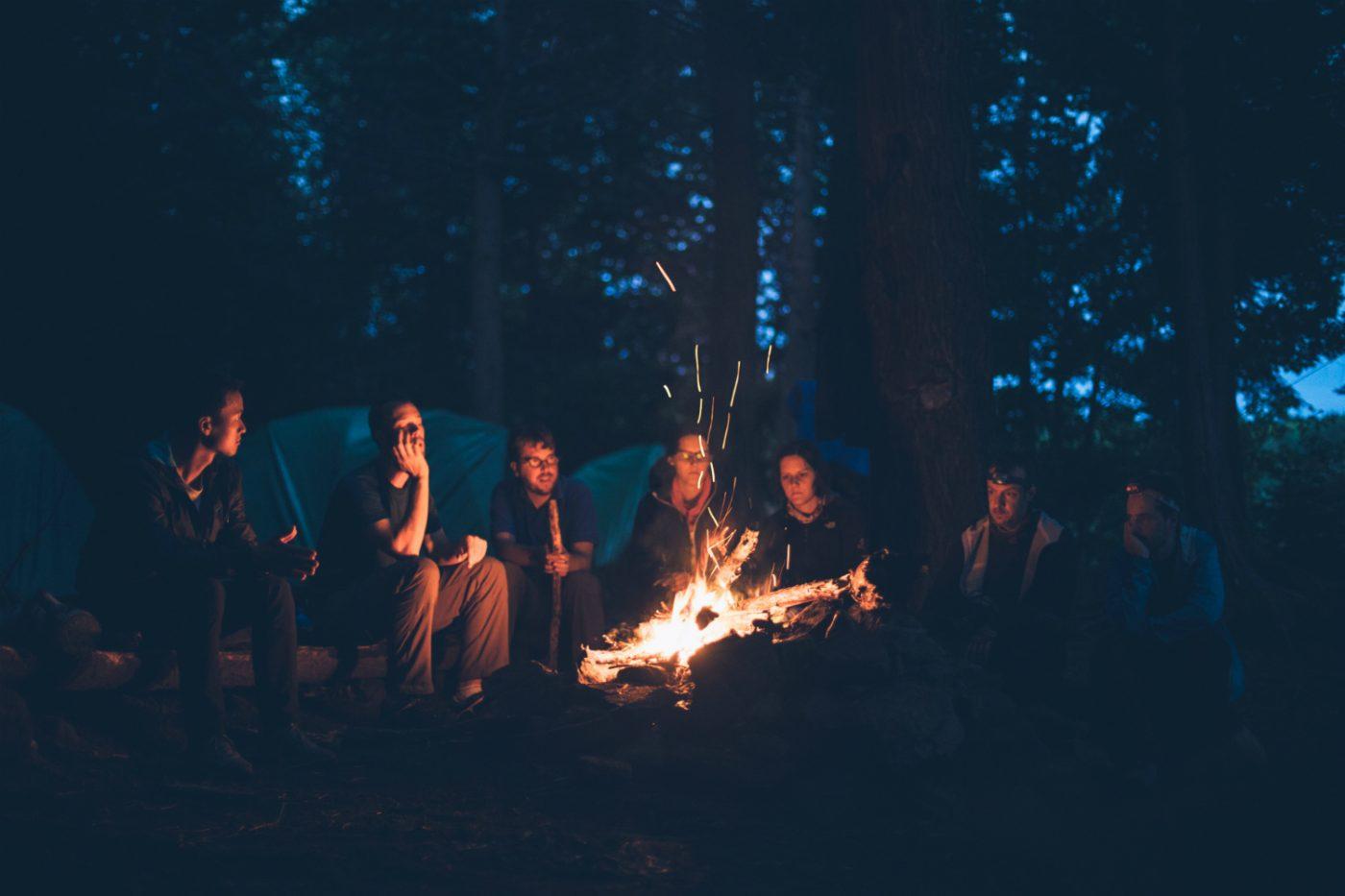 Eine Gruppe von Menschen sitzt um ein Lagerfeuer. Im Hintergrund sind Zelte zu sehen.