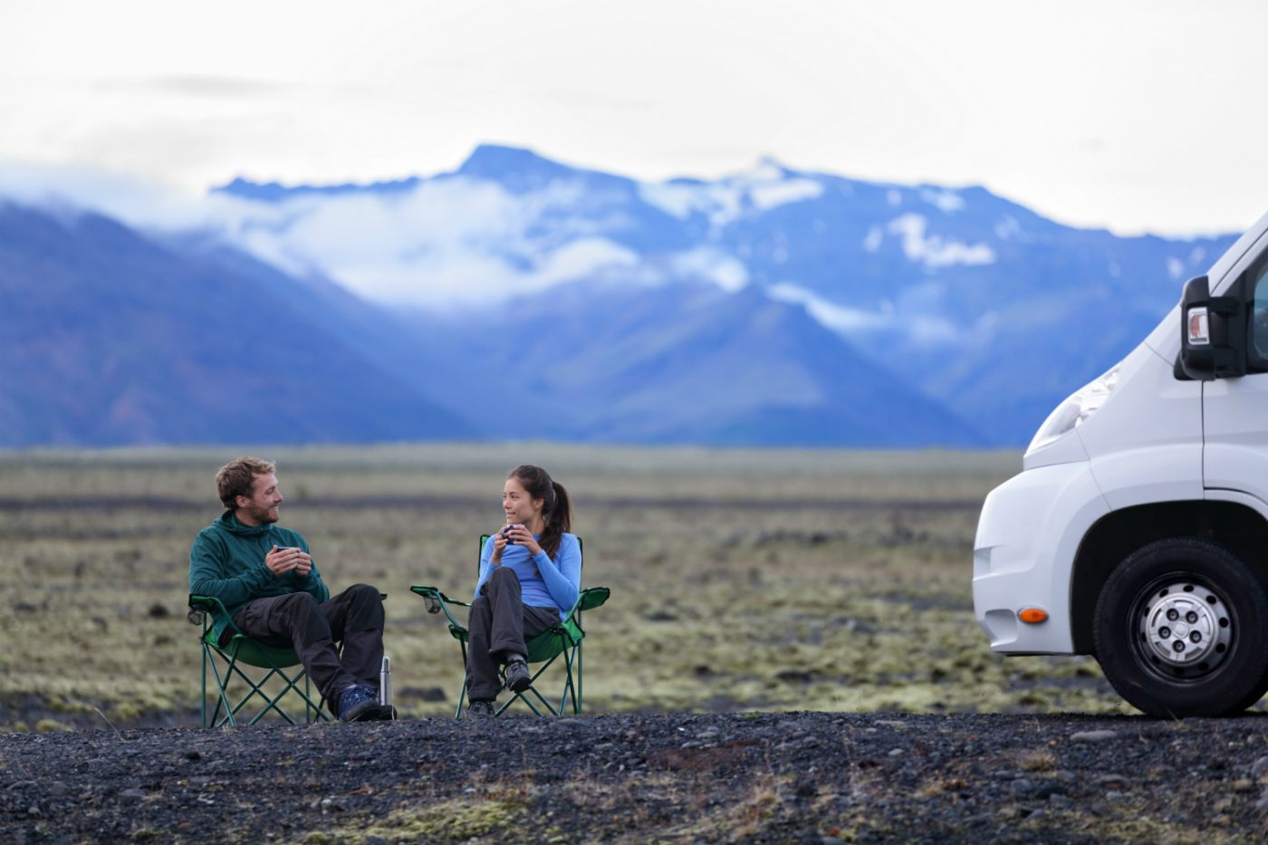 Ein Paar sitzt auf Campingstühlen neben einem Wohnmobil inmitten der Landschaft Islands.
