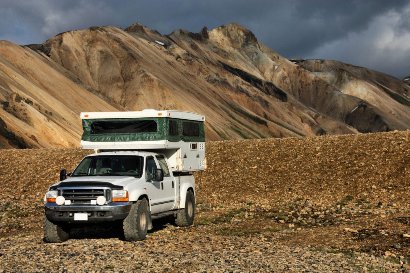 Ein Pickup mit Wohnmobil-Aufsatz in steiniger Umgebung.