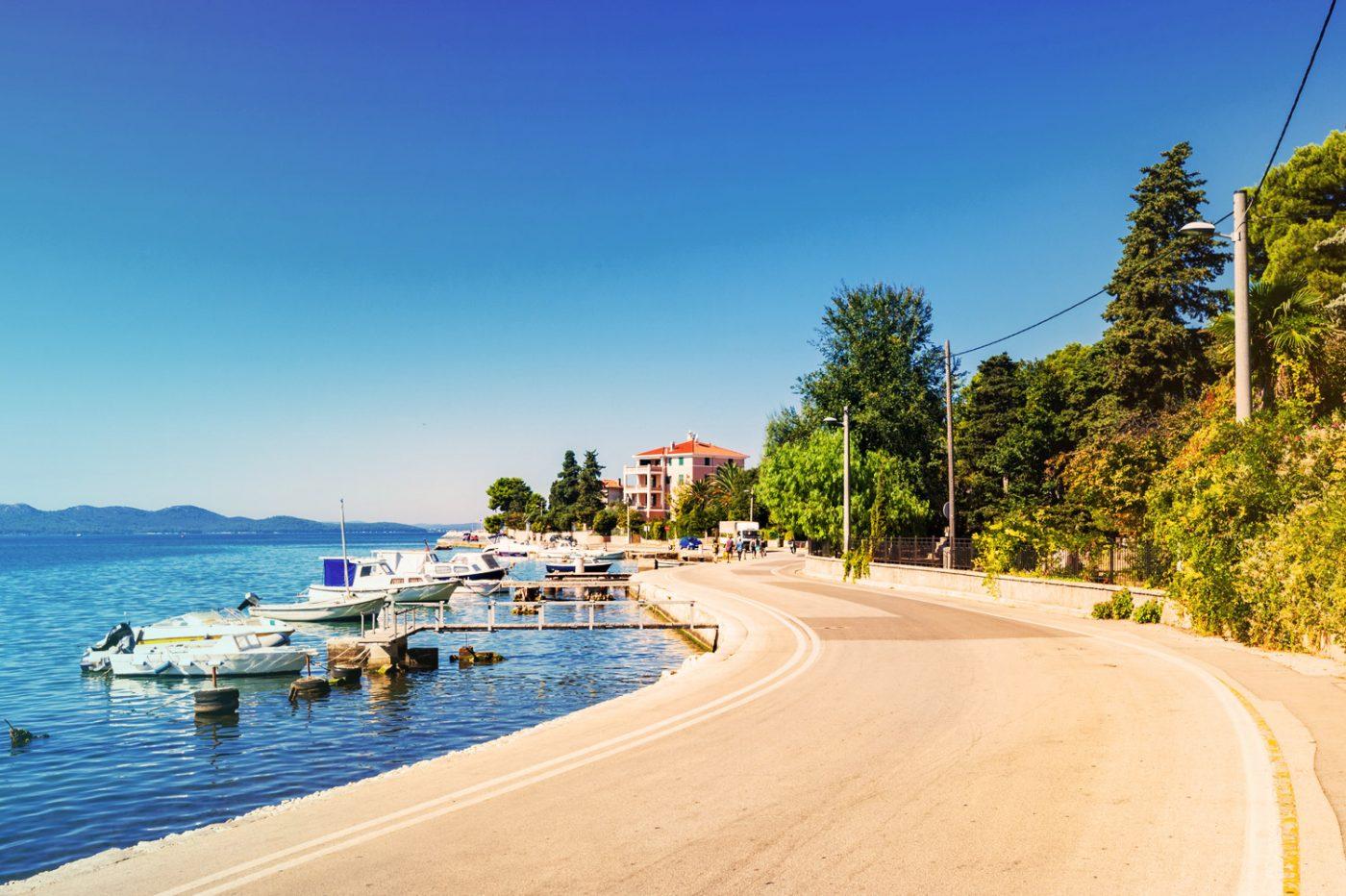 Eine Straße in Zadar, die direkt am Wasser gelegen ist.