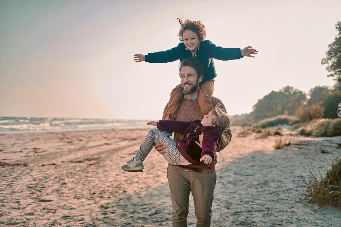 Ein Mann und zwei Kinder am Strand.