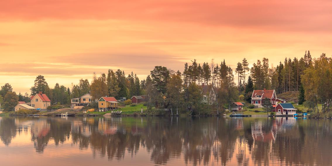 Bunte Häuser an einem See in der Region Dalarna, Schweden.