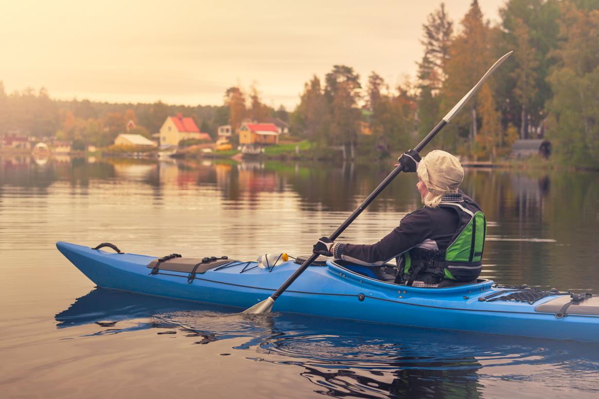 Eine Frau paddelt in einem Kanu auf einem See in Schweden.
