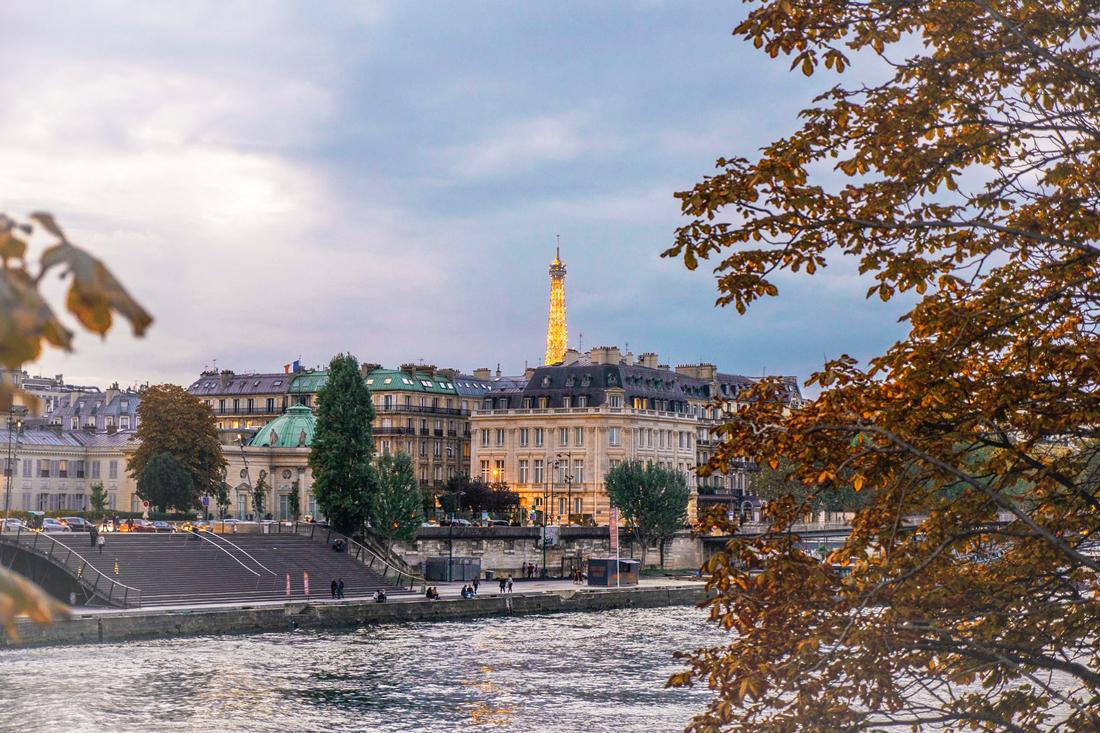 Die Seine, Gebäude und im Hintergrund die Spitze des Eifelturms in Paris, Frankreich.