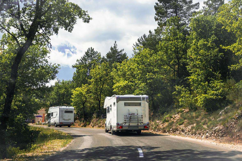 Zwei Wohnmobile auf einer Straße in Frankreich.