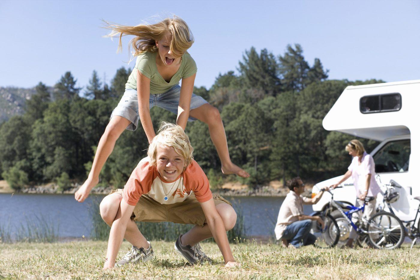 Zwei Kinder spielen gemeinsam, während im Hintergrund ein Paar vor einem Wohnmobil zu seheh ist.