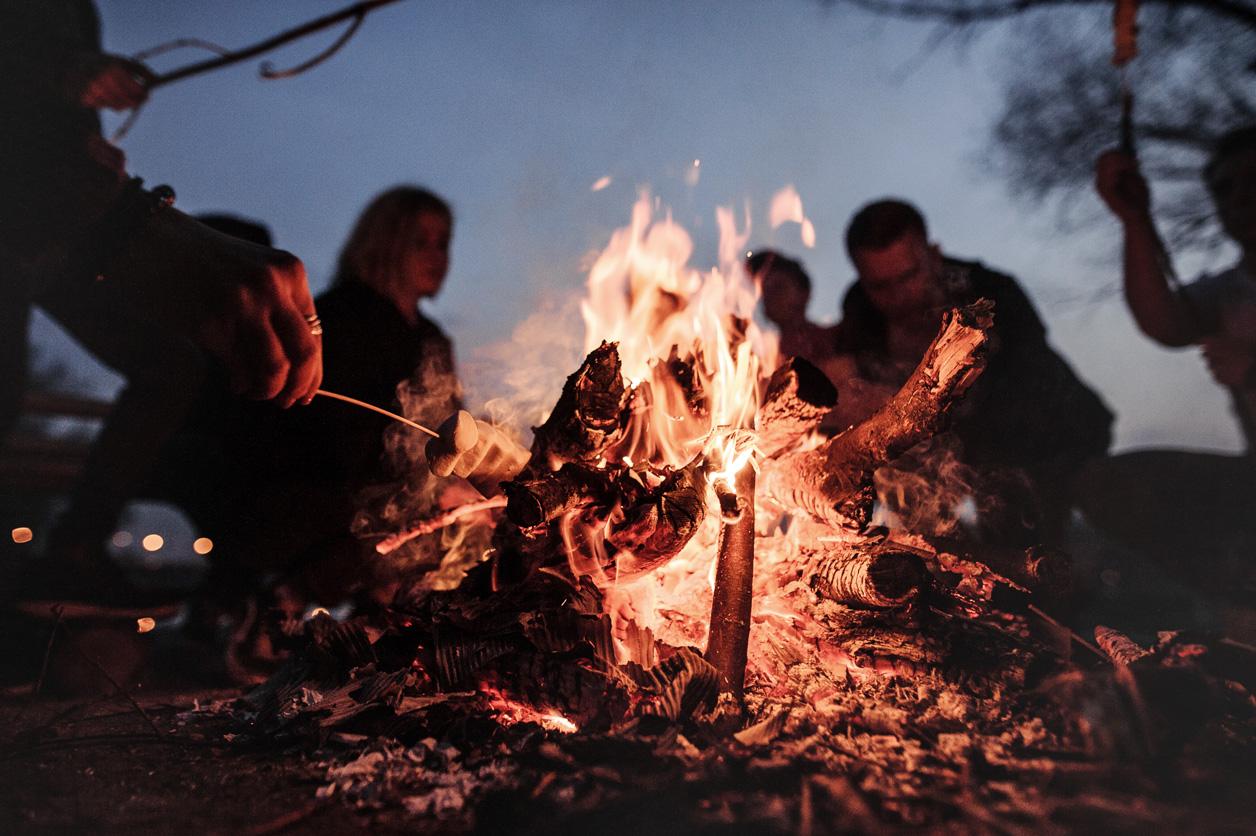 Eine Gruppe von Menschen sitzt um ein Lagerfeuer herum.