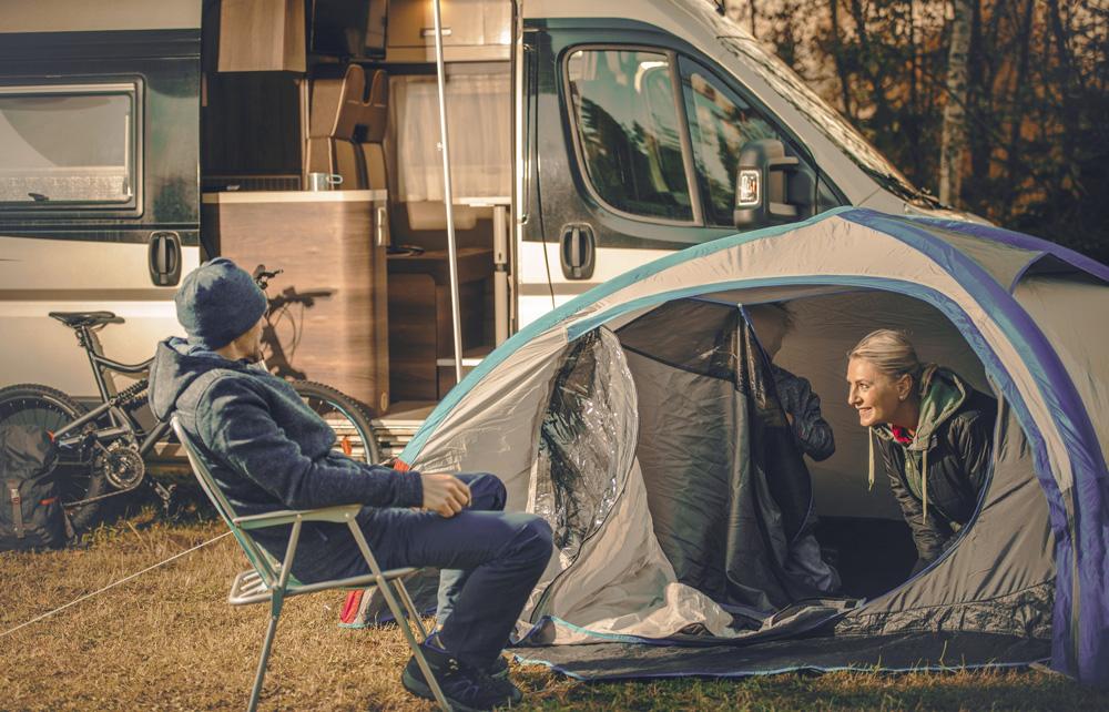 Drei Menschen bauen ein kleines Zelt auf. Im Hintergrund ist ein Wohnmobil zu sehen.