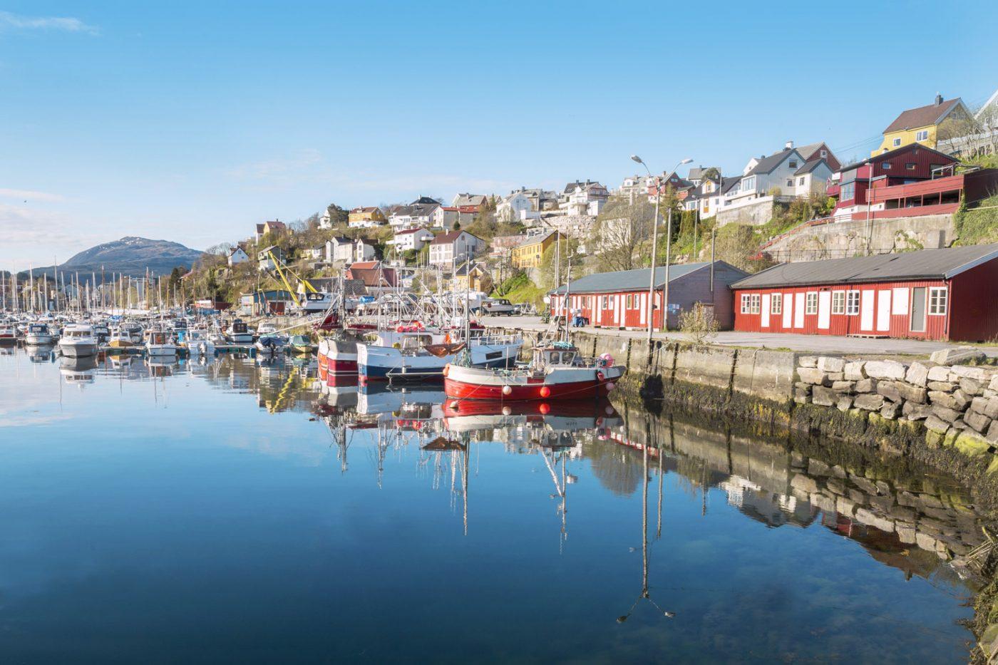 Der Hafen von Kristiansand mit vielen kleinen Booten und zahlreichen bunten Häuschen im Hintergrund.
