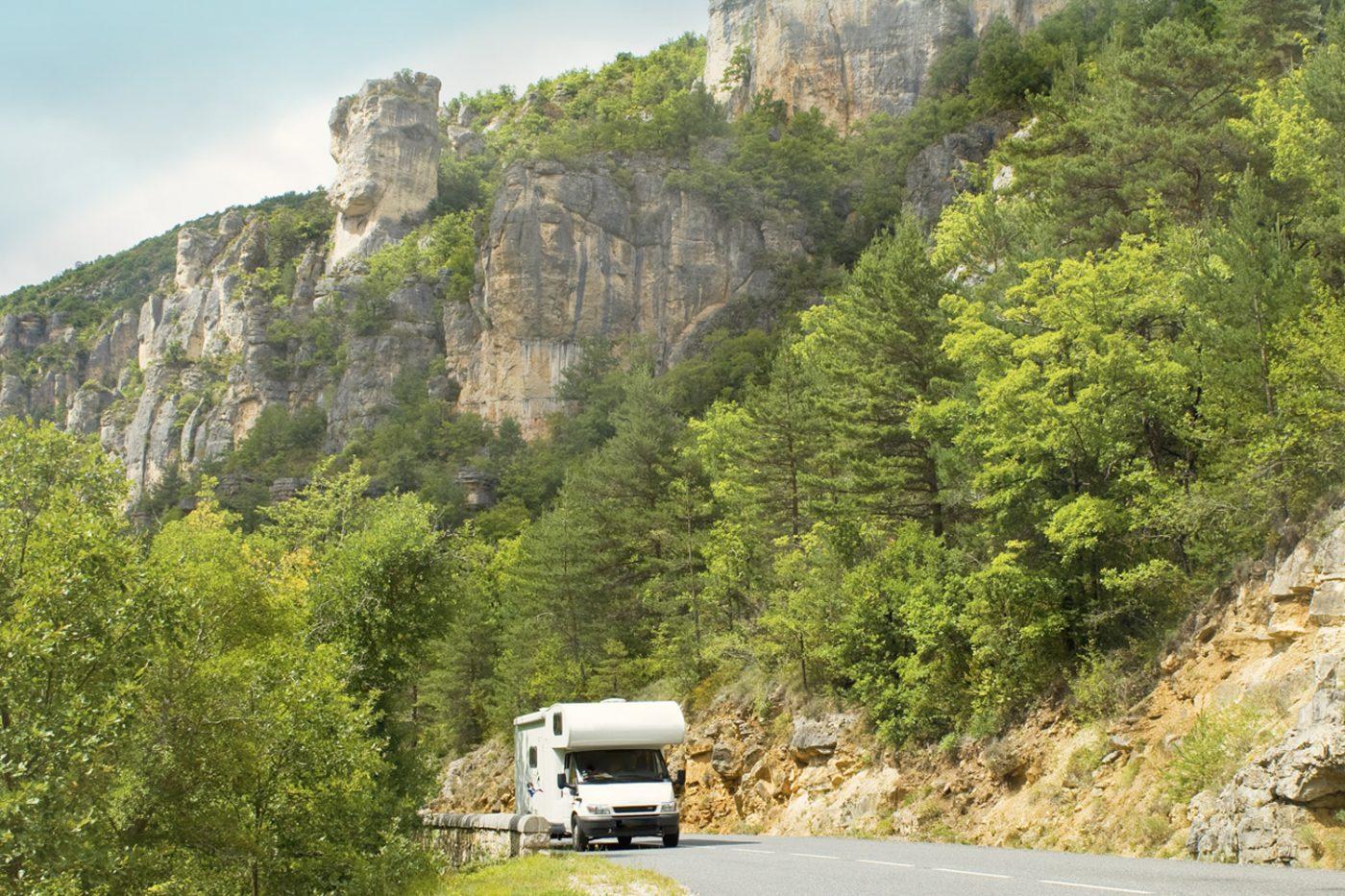 Ein Wohnmobil fährt entlang einer bewaldeten Steilwand in Frankreich.