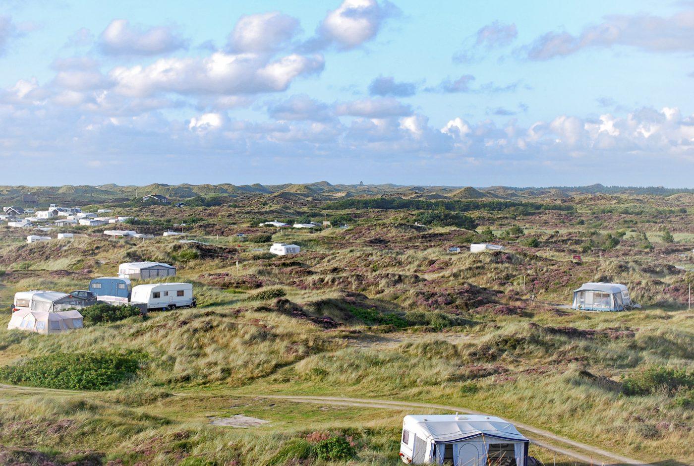 Wohnwagen und Zelte zwischen Dünen in Dänemark.