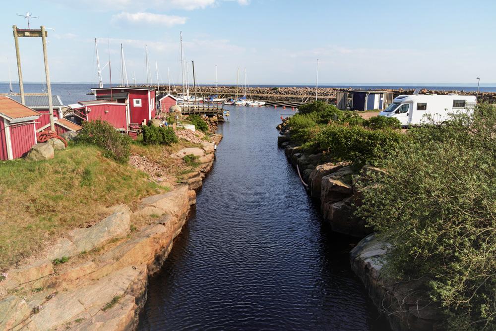 Rote, schwedische Häuser und ein Wohnmobil sind am Wasser zu sehen.