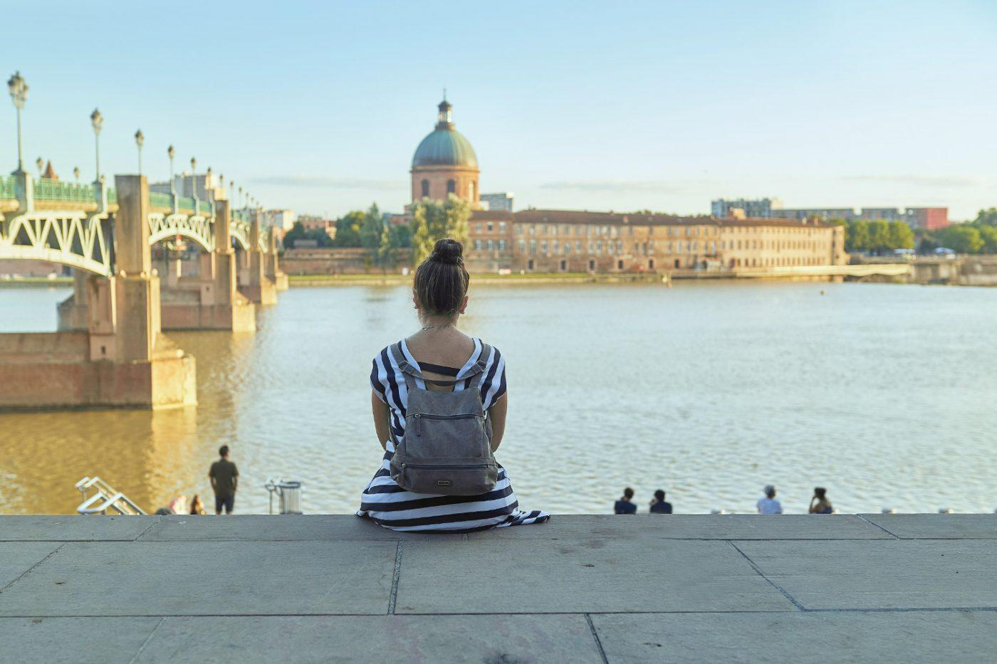 Eine Frau sitzt am Ufer des Fluss Garonne in Toulouse, Frankreich.