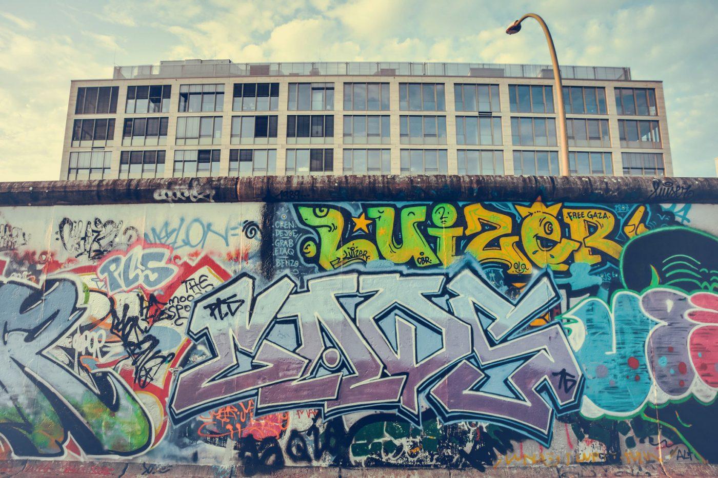 Ein Stück der Berliner Mauer, das mit Graffiti besprüht ist.