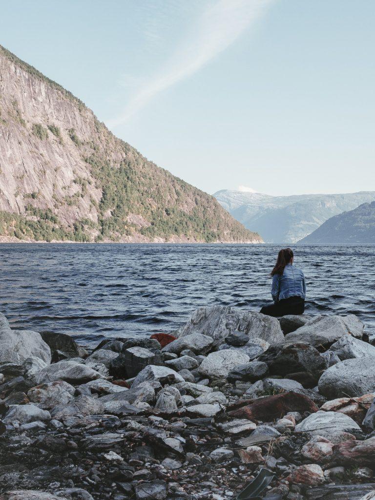 Ein Frau sitzt am Ufer eines Fjordes in Norwegen.