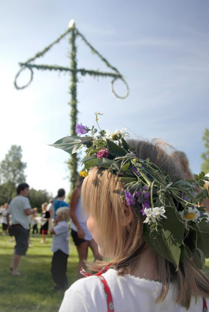 Ein blondes Kind mit einem Blumenkranz bei einem Midsommar-Fest.