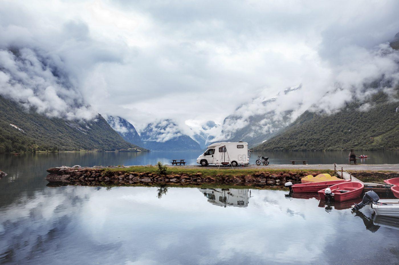 Ein Wohnmobil steht vor der beeindruckenden Kulisse eines Fjordes in Norwegen.