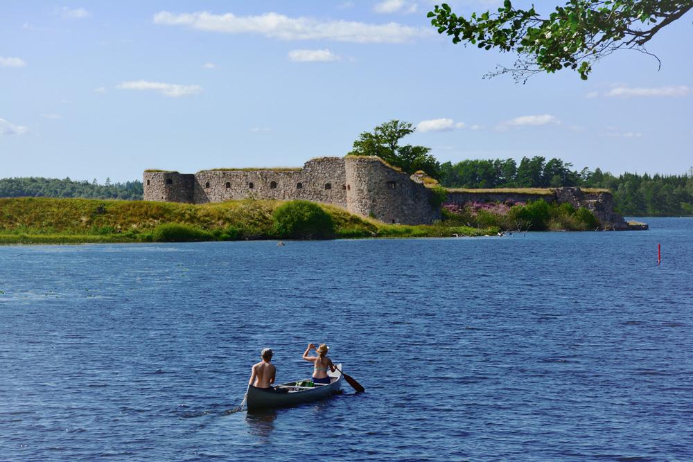 Zwei Kanu-Fahrer vor der Schlossruine Kronoberg bei Växjö, Schweden.
