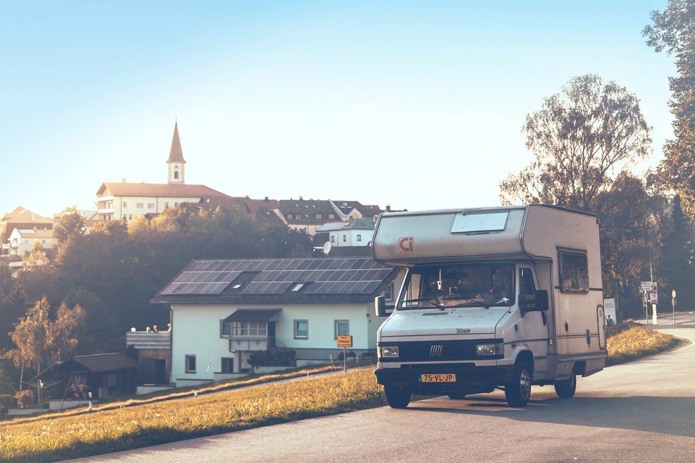 Ein Wohnmobil auf einer Straße in oder nahe einer Ortschaft.