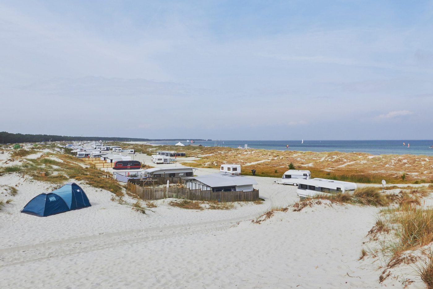 Mehrere Wohnmobile am Strand in den Dünen an der Ostsee.