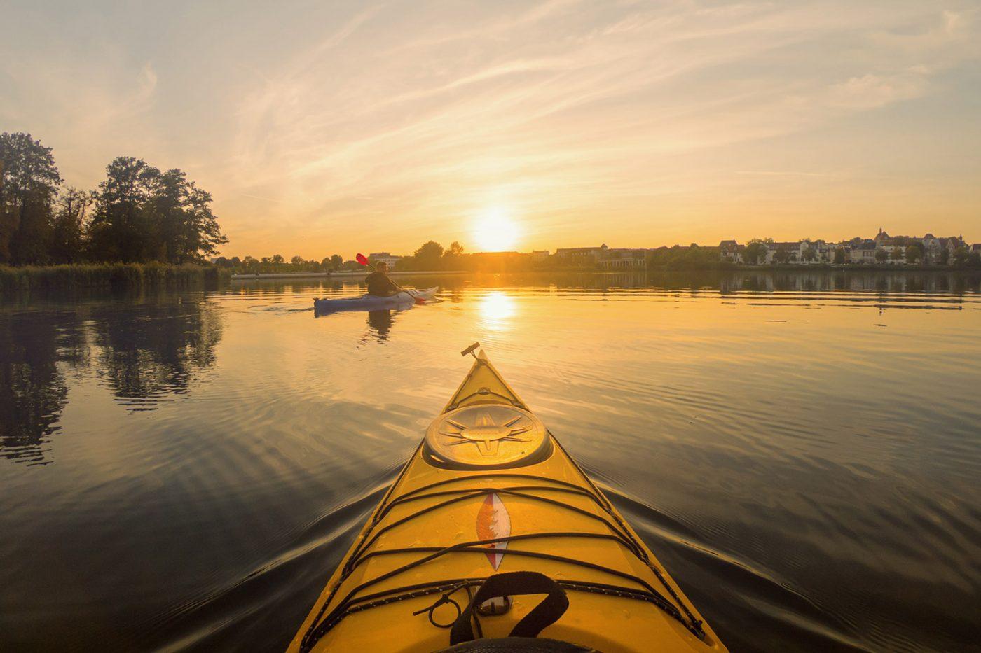 Ein Kajak bei Sonnenuntergang und ein Paddler im Hintergrund.